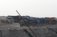 Gravel trucks lined up outside the gate