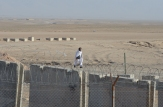 An Afghan man walking past the wall