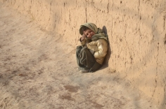 A little boy giving my the thumbs up as he huddled against the wall near FOB Bullard