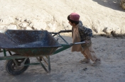 An Afghan boy pushes his wheelbarrow up the street in Jamalkhel