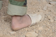 Ill-fitting shoes and sandals are a common sight, no matter the temperature. This is an Afghan Soldier preparing to go on patrol with us.