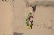The girls peeking out of teh doorway during a village shura in Taj Murani