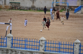 The kids are playing soccer on the muddy field at their school, wearing sandals