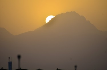 The sun slipping behind the hilltop
