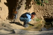 An Afghan Policeman who joined us on the mission washes his face in the karez